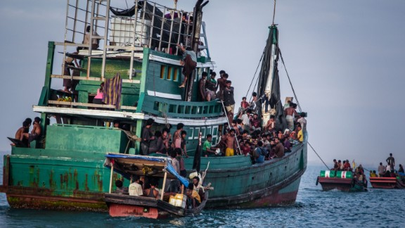 A green fishing vessel in the ocean. Refugees are crowded onto the decks and there are several smaller fishing vessels with refugees beside it in the water.