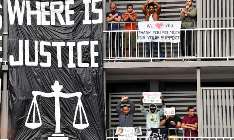 """Refugees protest on a hotel balcony in Brisbane. Some hold signs and others stand with their arms crossed on their chest. There is a large black and white banner that says, """"Where is Justice"""" that hangs beside them."""