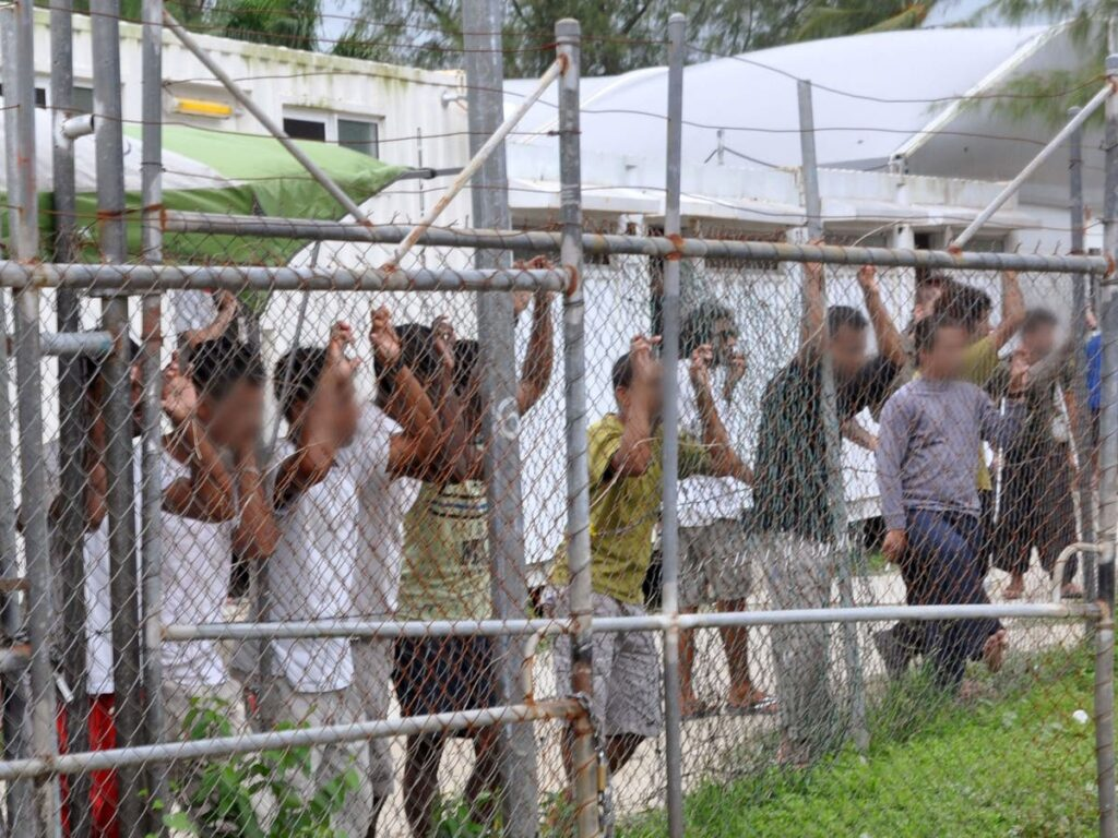 Refugees stand against a wire fence in Manus, PNG. Their faces are blurred.